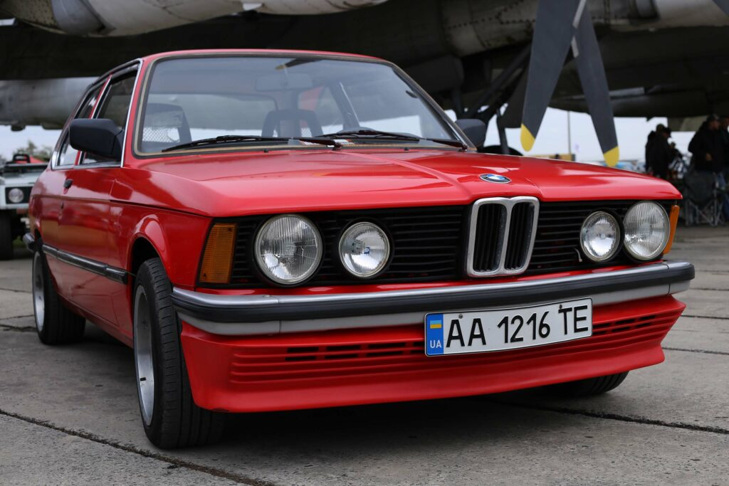red BMW classic car with airplane in background
